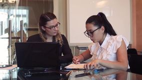 A team of two business girls working on a business project in the office using a mobile computer. A team of two young beautiful business girls wearing glasses stock footage