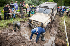 Team on Uaz 469 setting a recovery sand tracks to overcome a hard pit. Royalty Free Stock Image