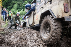 Team on Uaz 469 setting a recovery sand tracks to overcome a hard pit. Stock Photo
