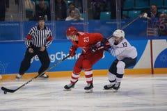 Team United States nel bianco nell'azione contro Team Olympic Athlete dal gioco rotondo preliminare del hockey su ghiaccio del `  Fotografie Stock