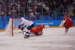 Team United States no branco na ação contra Team Olympic Athlete do jogo redondo preliminar do hóquei em gelo do ` s dos homens d Imagens de Stock Royalty Free