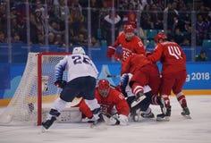 Team United States no branco na ação contra Team Olympic Athlete do jogo redondo preliminar do hóquei em gelo do ` s dos homens d Fotos de Stock Royalty Free