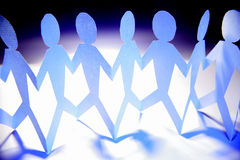 Team unity. Line of connected paper dolls symbolizing team or group unity in business or family Royalty Free Stock Photos
