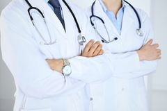 Team of unknown doctors standing straight with arms crossed in hospital. Physicians ready to help. Healthcare, insurance. And medicine concept royalty free stock photo