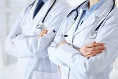 Team of unknown doctors standing straight with arms crossed in hospital. Physicians ready to help. Healthcare, insurance. And medicine concept royalty free stock photography
