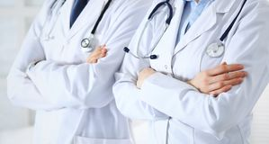 Team of unknown doctors standing straight with arms crossed in hospital. Physicians ready to help. Healthcare, insurance. And medicine concept royalty free stock images