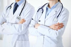 Team of unknown doctors standing straight with arms crossed in hospital. Physicians ready to help. Healthcare, insurance. And medicine concept stock image