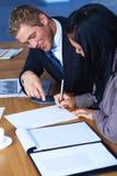 Team van 2 bedrijfsmensen die aan documenten werken Stock Afbeelding
