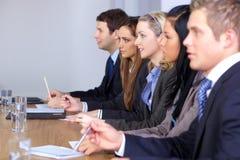 Team van 5 mensen die bij conferentielijst zitten Stock Afbeelding