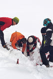Team van alpiene redders die in sneeuw graven stock fotografie