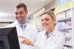 Team van apothekers die computer bekijken stock foto's