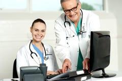 Team van artsen die aan computer werken Stock Afbeeldingen