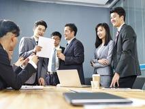 Team van Aziatische bedrijfsmensen die in bureau samenwerken stock afbeeldingen