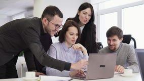 Team van bedrijfsmensen die laptop het scherm tijdens creatieve vergadering bekijken stock video