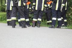Team van Brandbestrijders die pauzerend enkel Voeten bespreken Stock Fotografie