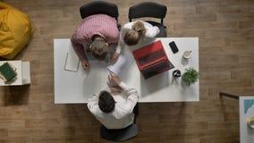 Team van drie jonge bedrijfsmensen die en project bespreken die, topshot, bij lijst in modern bureau zitten binnenkomen stock video