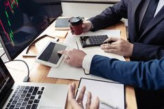 Team van effectenmakelaars die met de vertoningsschermen bespreken die gegevens, grafieken en rapporten van effectenbeurs handel  royalty-vrije stock fotografie