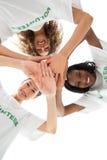 Team van gelukkige vrijwilligers die handen samenbrengen en neer camera bekijken stock fotografie