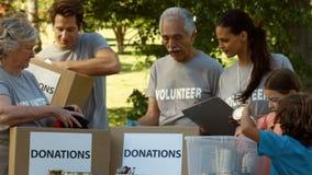 Team van gelukkige vrijwilligers die schenkingen verzamelen stock videobeelden