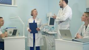 Team van gemengd medisch personeel die in het bureau lachen Stock Foto's