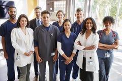 Team van gezondheidszorgarbeiders bij het ziekenhuis die aan camera glimlachen stock afbeelding
