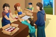 Team van het vrijwilligers werken op het centrum van de voedselschenking Stock Afbeeldingen