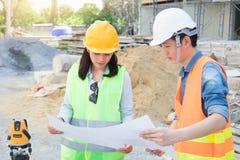 Team van ingenieurs die gele helm dragen en bij bouwwerf werken stock fotografie