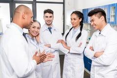 Team van jonge artsen in laboratoriumlagen die het werk bespreken royalty-vrije stock afbeeldingen