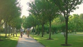 Team van jonge fietsers die fietsen in park berijden stock video