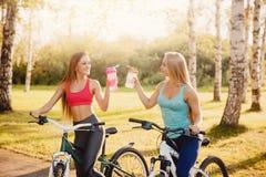 Team van meisjesfiets met fles water in park op zonsondergangachtergrond royalty-vrije stock foto
