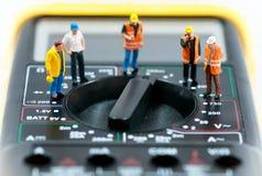 Team van miniatuurarbeiders bovenop multimeter Grote details! Stock Foto's