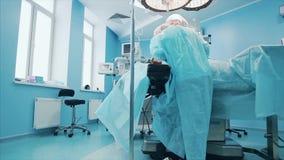Team van professionele chirurgen die invasieve chirurgie op een patiënt in de het ziekenhuis werkende ruimte uitvoeren De chirurg stock videobeelden