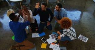 Team van stafmedewerkers die hoogte vijf geven aan elkaar in de vergadering stock footage