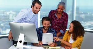 Team van stafmedewerkers die over digitale tablet bespreken stock video