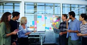 Team van stafmedewerkers die over kleverige nota's bespreken stock videobeelden