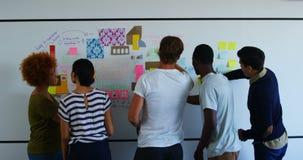 Team van stafmedewerkers die over kleverige nota's over whiteboard bespreken stock videobeelden