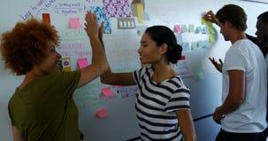 Team van stafmedewerkers die over kleverige nota's over whiteboard bespreken stock video