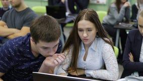 Team van studenten bij de praktische opleiding in het klaslokaal Het meisje verklaart aan uw vrienden de essentie van taak, tonen stock video