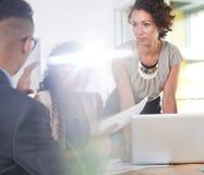 Team van succesvolle bedrijfsmensen die een vergadering in uitvoerend zonovergoten bureau hebben royalty-vrije stock foto