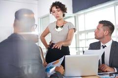 Team van succesvolle bedrijfsmensen die een vergadering in uitvoerend zonovergoten bureau hebben stock foto