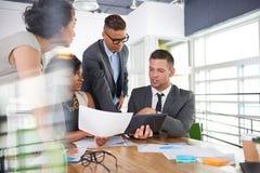 Team van succesvolle bedrijfsmensen die een vergadering in uitvoerend zonovergoten bureau hebben Royalty-vrije Stock Fotografie