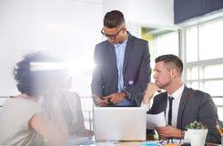 Team van succesvolle bedrijfsmensen die een vergadering in uitvoerend zonovergoten bureau hebben stock afbeelding