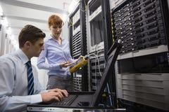 Team van technici die digitale kabelanalisator op servers gebruiken Stock Afbeelding