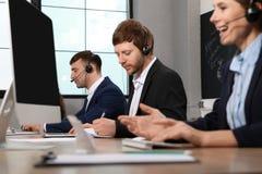 Team van technische ondersteuning met hoofdtelefoons stock foto