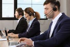 Team van technische ondersteuning met hoofdtelefoons royalty-vrije stock afbeelding