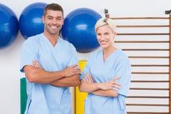 Team van therapeuten met wapens het glimlachen bij camera worden gekruist die Stock Foto