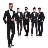 Team van vijf groomsmen in tuxedoes met leider vooraan royalty-vrije stock foto