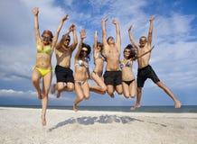Team van vrienden die bij het strand springen Royalty-vrije Stock Afbeeldingen