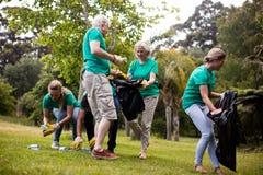 Team van vrijwilligers die draagstoel opnemen royalty-vrije stock foto's