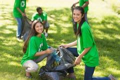 Team van vrijwilligers die draagstoel in park opnemen stock fotografie